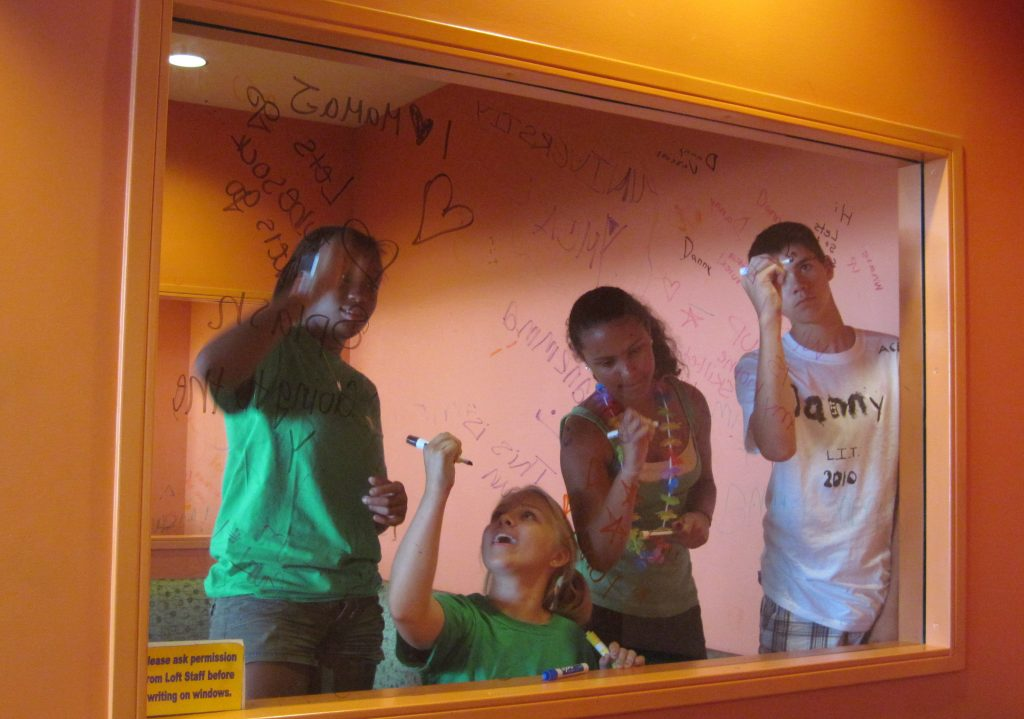 Teens let their creativity flow in the form of window writing in a library teen space