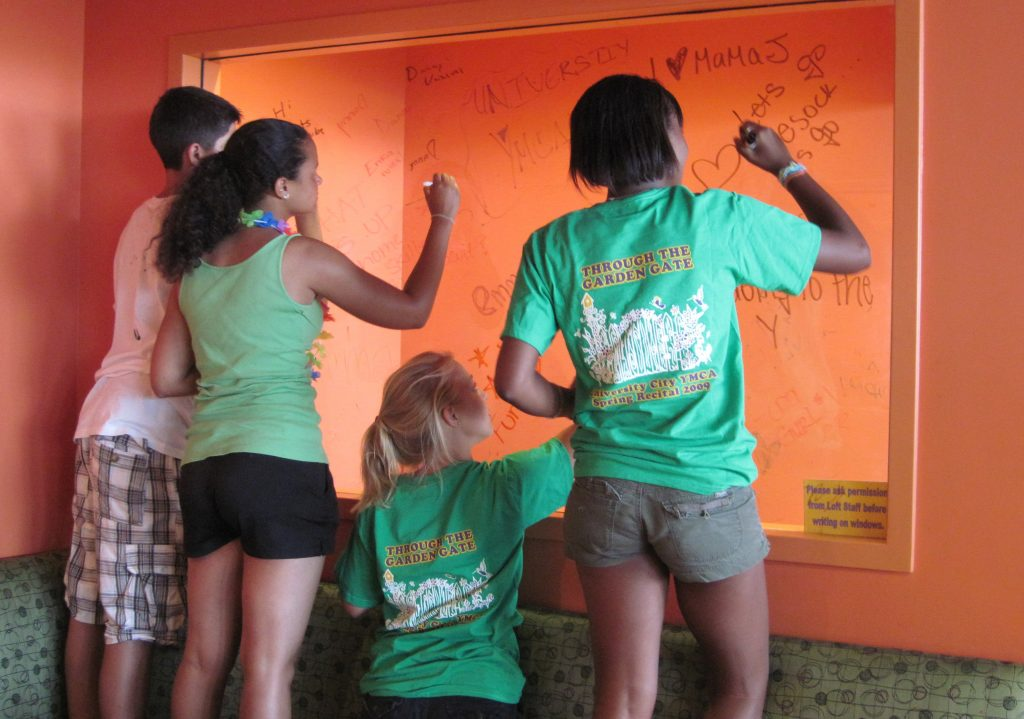 Teens let their creativity flow in the form of window writing in a library teen space.